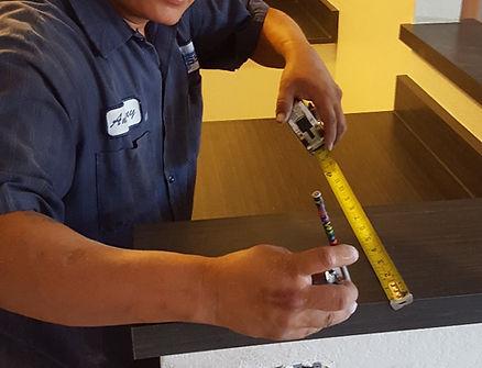 Installer measuring countertops for laminate installation