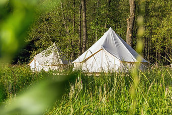 Two white bell tents outdoors