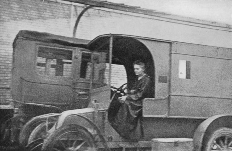 Marie Curie dentro de um caminhão. Foto em preto e branco.