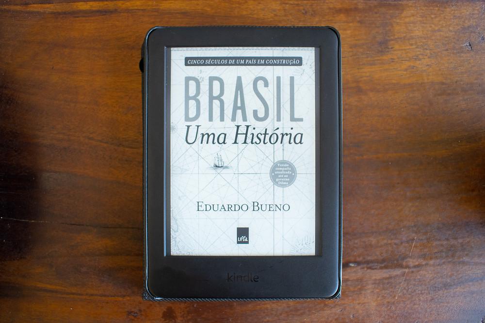 Um kindle com a capa do livro Brasil: Uma História em cima de uma mesa de madeira.