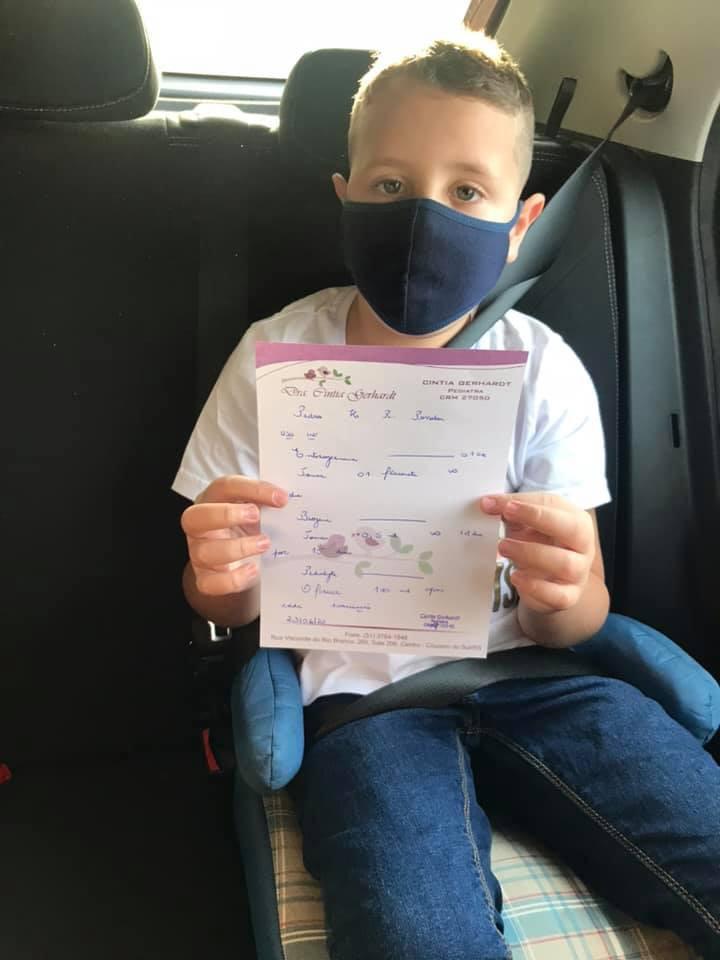 Um menino segurando uma receita médica e de máscara.