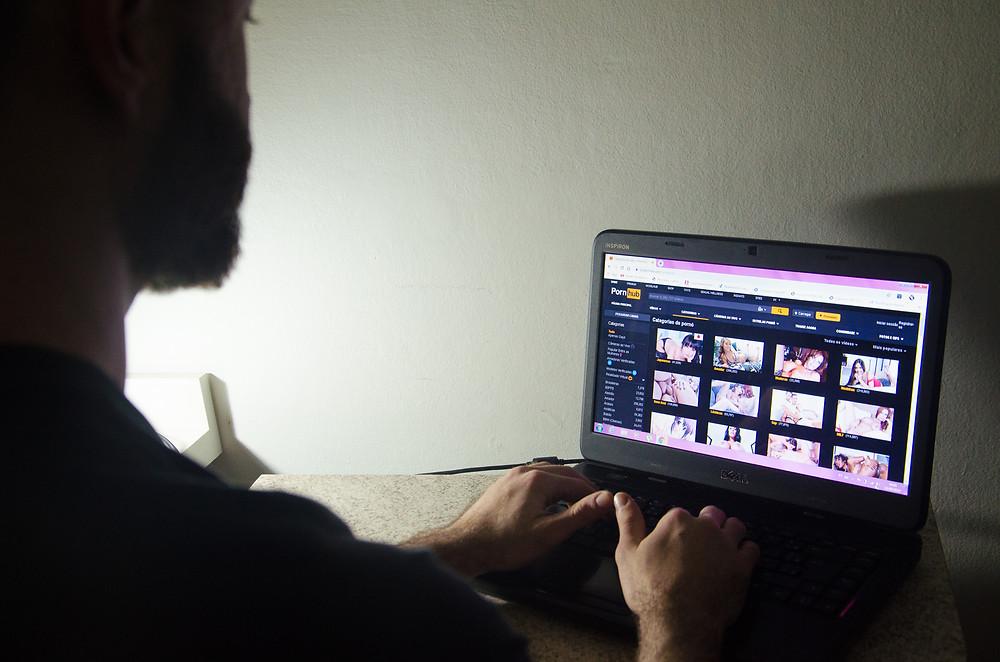 Um homem em frente a um notebook, com um site pornô aberto.