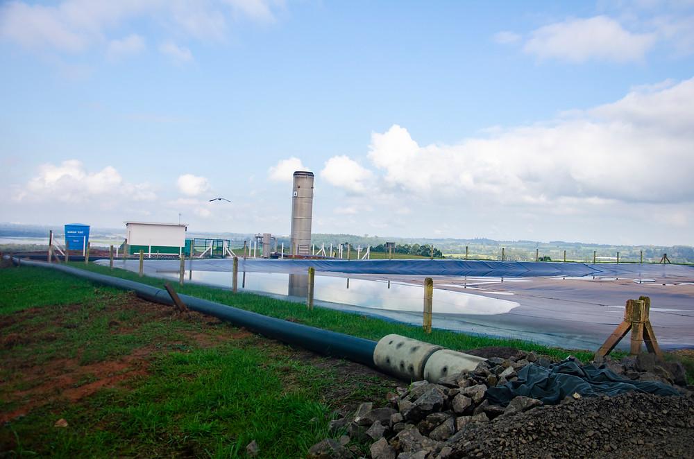 A foto mostra canos que levam o biogás e a torre onde ele é queimado