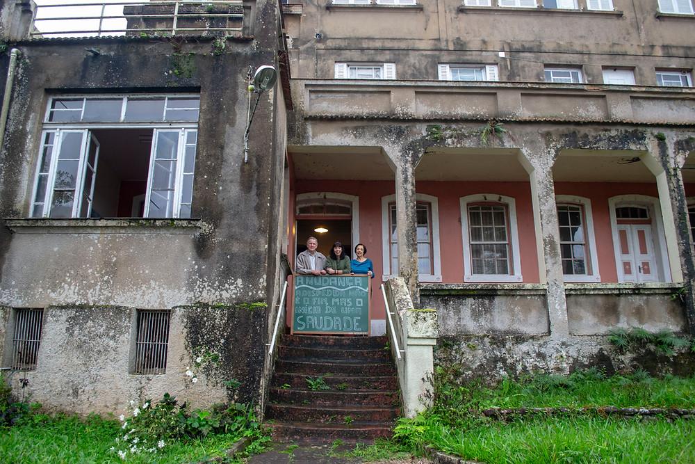 """Uma família em frente a uma casa antiga, com """"A mudança: a despedida não é o fim, mas o início de uma saudade""""."""
