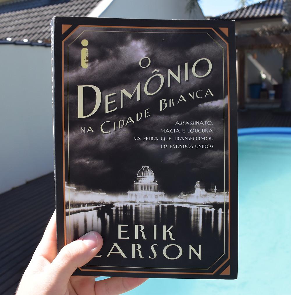 Uma mão segura um livro em frente a uma piscina.