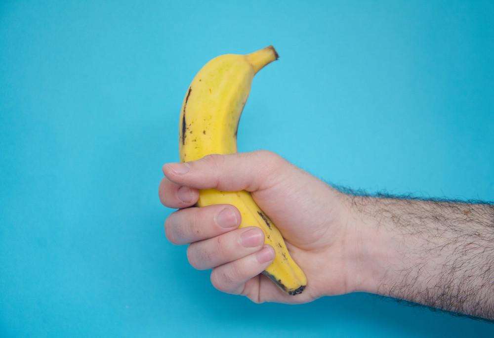 Uma mão segurando uma banana.