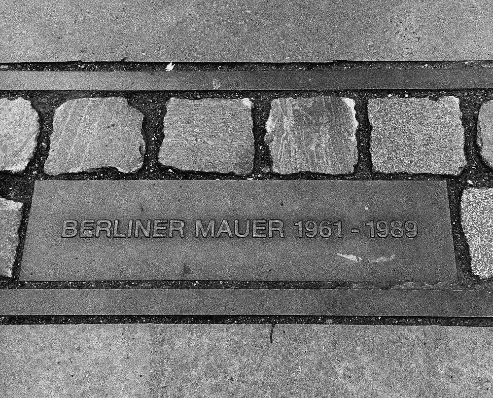Um monumento no chão com o inscrito Berliner Mauer 1961-1989.