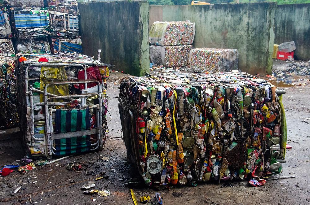 Fardos de materiais recicláveis, com latinhas, cadeiras e vários outros objetos, cercados por sujeira