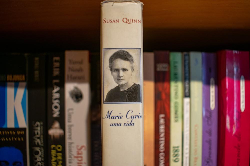 A lombada do livro Marie Curie se destacando em meio aos outros da estante.