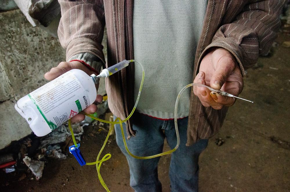 Um homem segura uma seringa e um medicamento descartados de maneira inadequada