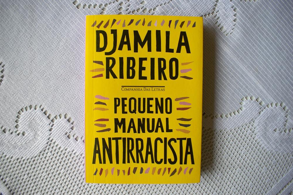 Livro Pequeno Manual Antirracista em cima de uma toalha de renda branca