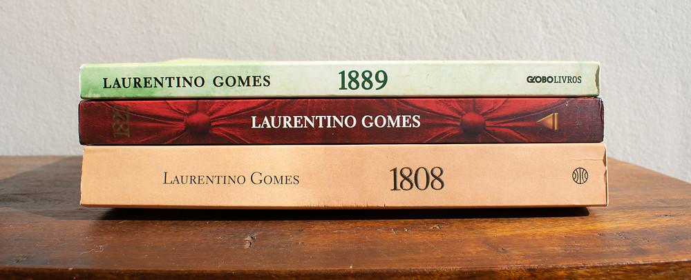Os livros 1808, 1822 e 1889 empilhados em uma mesa de madeira.