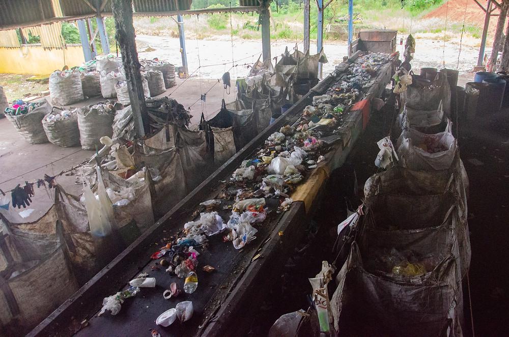 Um lugar sujo, onde ficam esteiras com lixos e sacolas de separação