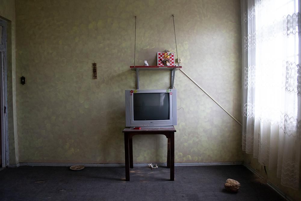Uma sala vazia, apenas com uma TV antiga.