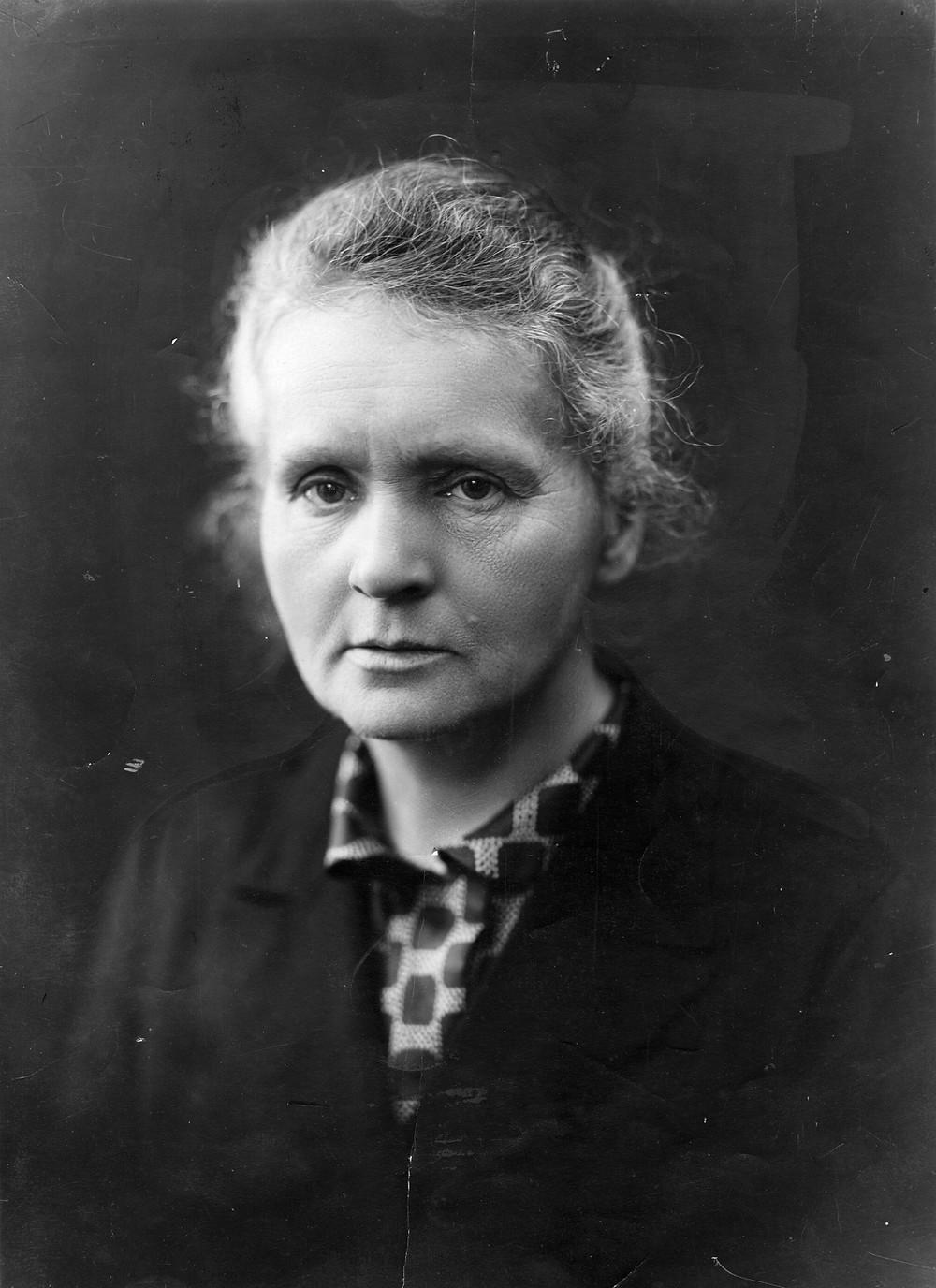 Uma mulher, em preto e branco, olha séria para a câmera.