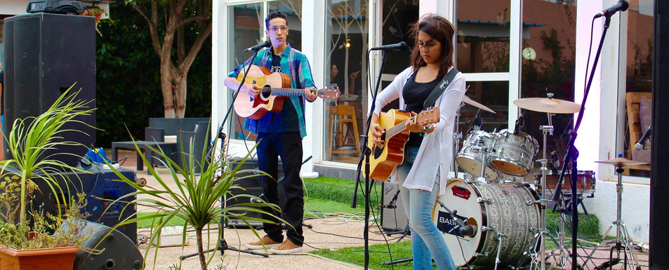 Concert sur une terrasse de restaurant devant le jardin et la piscine