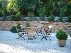 Pflasterfläche mit Natursteinmauer