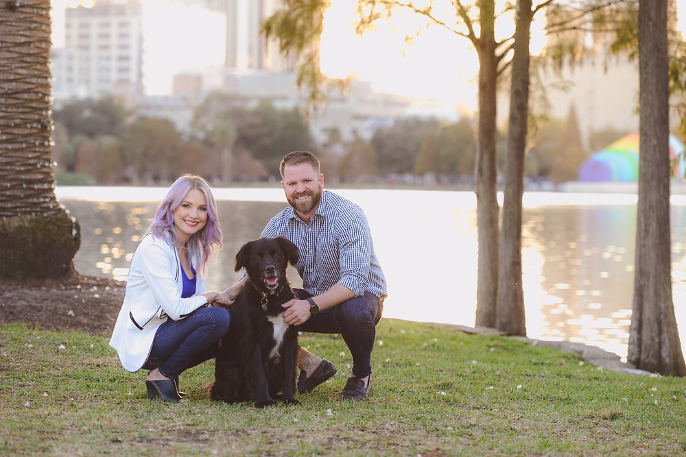 couple poses with their dog at Lake Eola in Downtown Orlando
