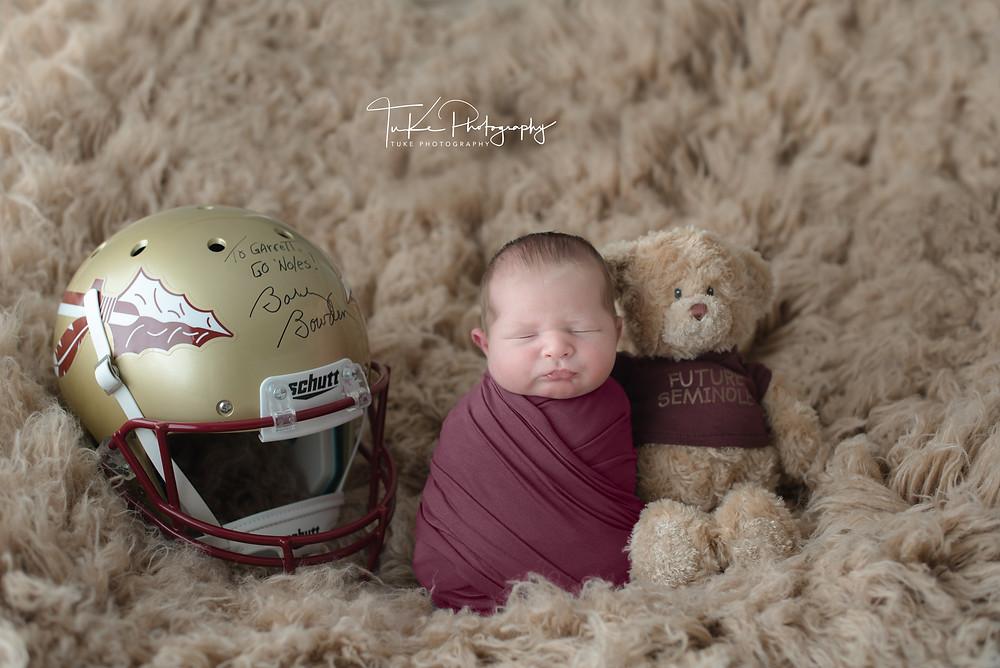 newborn baby boy with FSU helmet and teddy bear