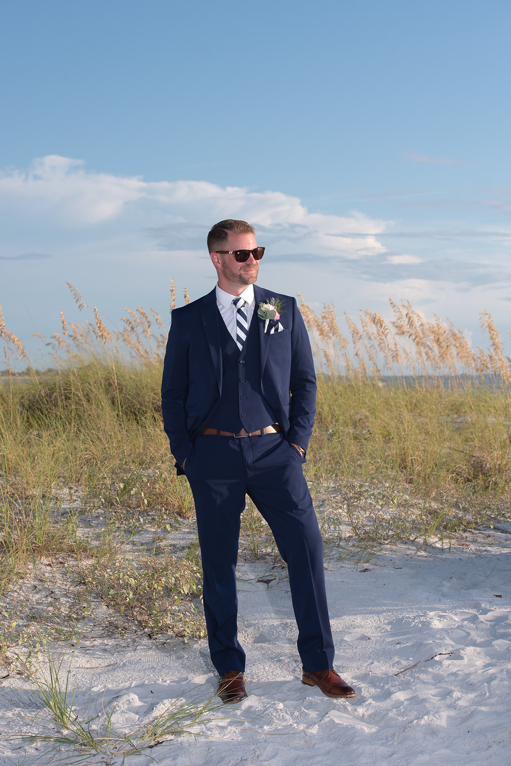 handsome groom poses for formal portraits taken on St Pete Beach in Florida