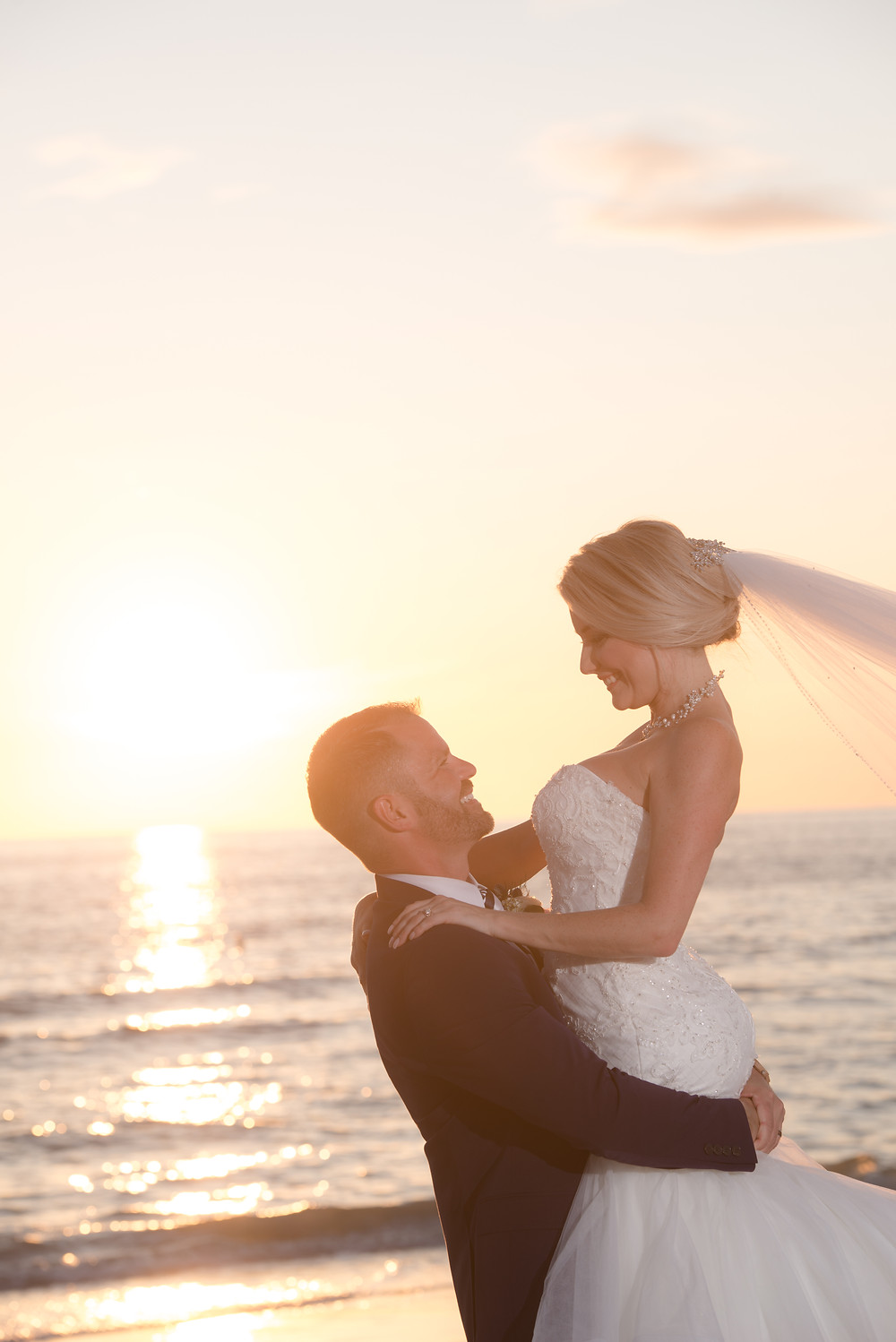 Groom lifts bride up during their sunset bridal portrait session on St Pete Beach in Florida