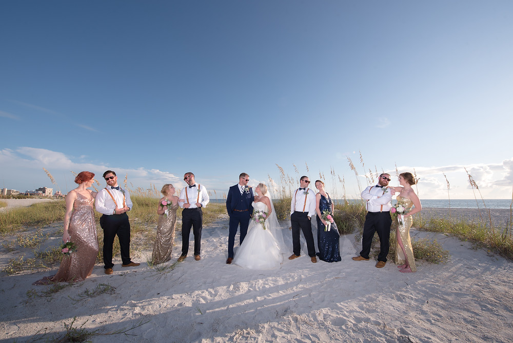 whole bridal party poses for photos on St Pete Beach in Florida