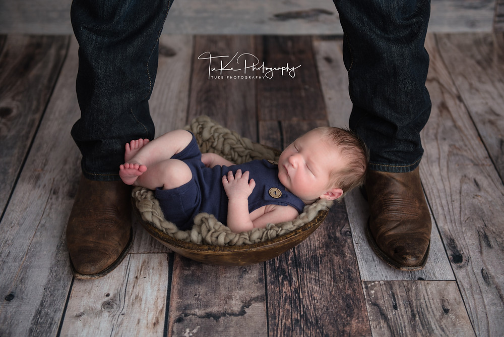 father with cowboy boots on and his newborn baby boy