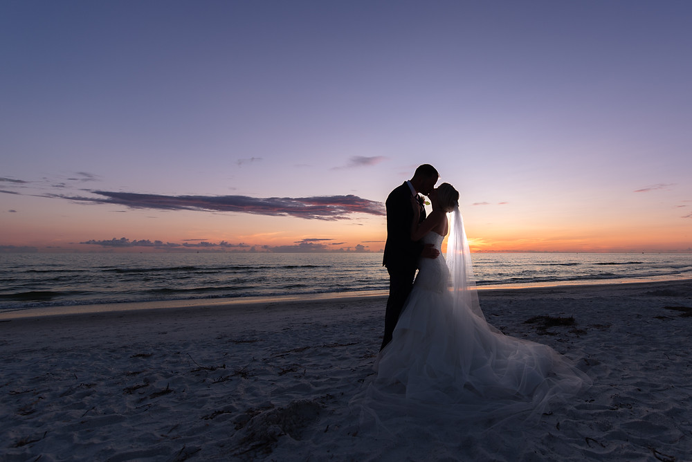 bride and groom kiss at sunset on St Pete Beach in Florida