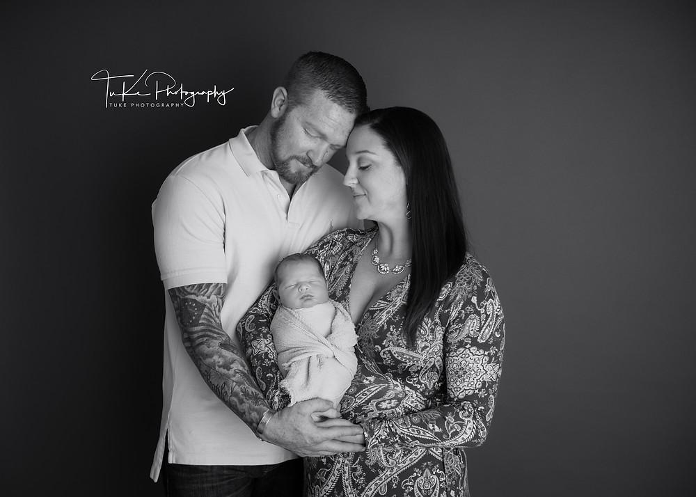 family with newborn baby boy hugging