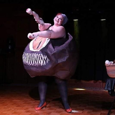 Jamie is dancing in a Beholder costume from Dungeons and Dragons.  She is smiling and holding Beholder eye stalks.