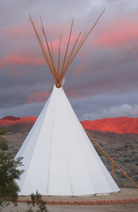 white tipi against a green and red mountain background with pink-tinged cloudy sky