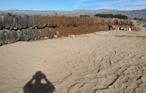 tire bale wall, partially covered in earth, with shadow of photographer in foreground