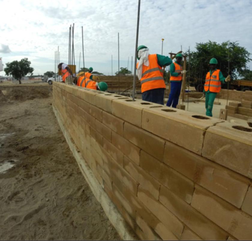 construction workers building a wall out of compressed earth blocks -- large tan bricks