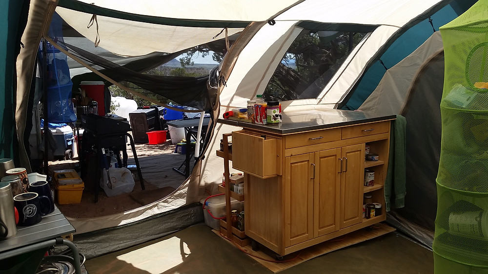 cabinet to right, looking out through tent door to stove, water, and open area