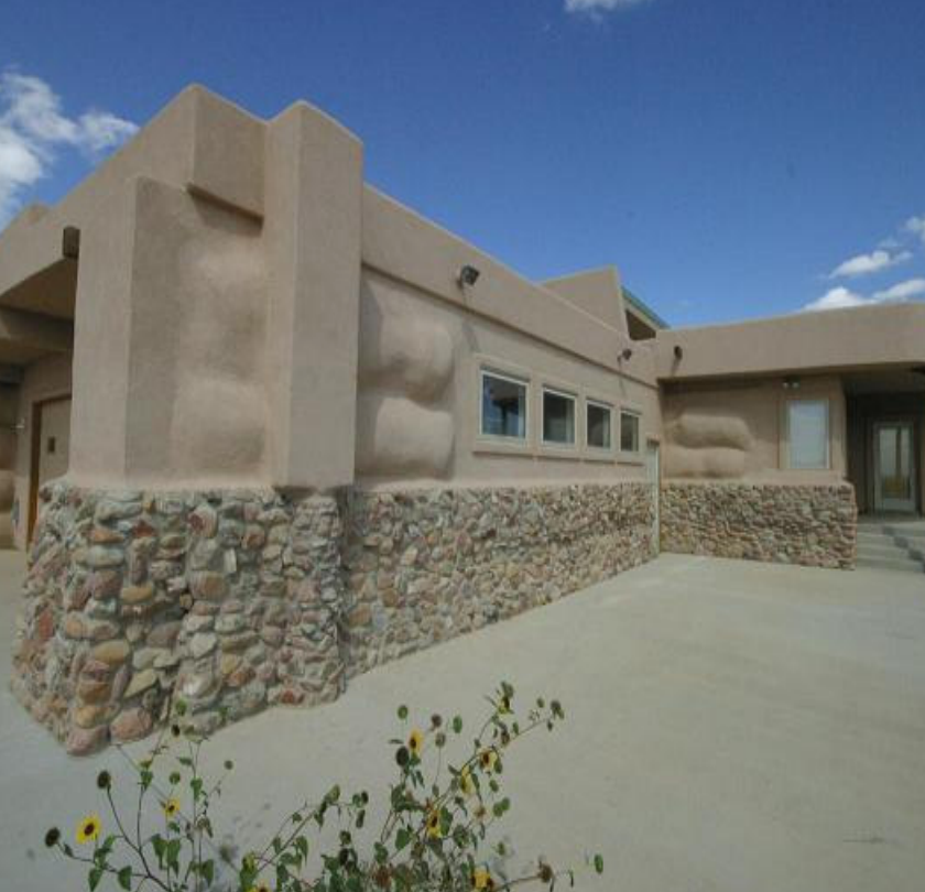 an adobe-style house with lumpy walls, showing off the tire bale structure underneath