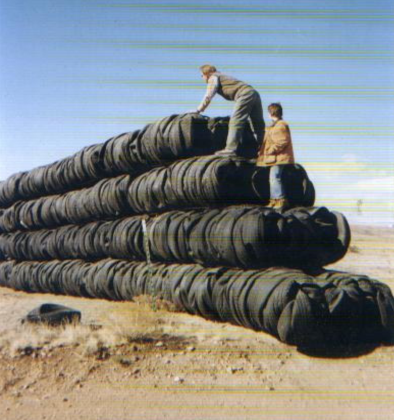 tire bales stacked 4-high to make a wall receding into the distance and stepping down toward this end; two people standing on the end of row 2 and row 3
