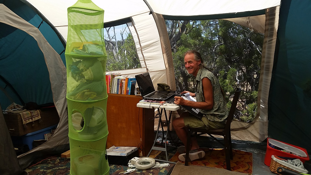 man at table with computer inside tent