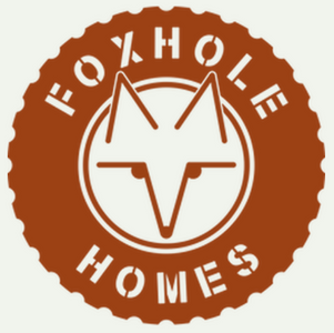 """logo of tire with fox in the center and """"foxhole homes"""" written in stencil text around the perimeter"""