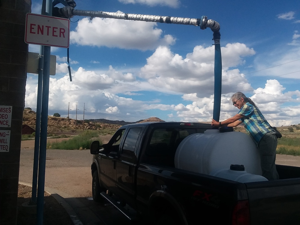 Woman in back of pickup filling big tank with water coming down from above.