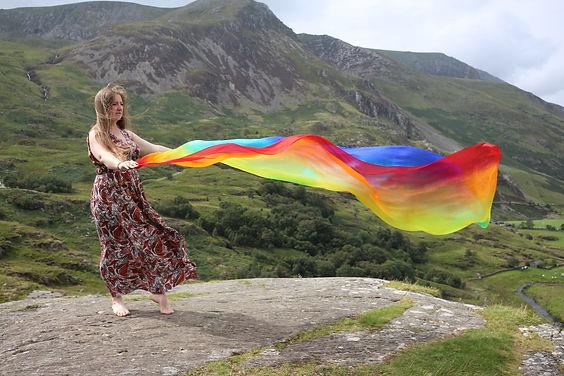 Rachel with rainbow fabric, under the dancing tree