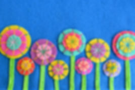 A row of colorful flowers on blue felt.