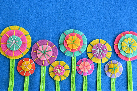 A row of colorful flowers on blue felt.