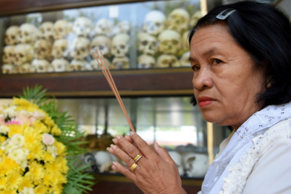 A woman prays during the annual 'Day of Remembrance' at the Choeung Ek killing fields memorial on May 20 recalling the horrors of the Khmer Rouge regime that ruled Cambodia from 1975-79. (Photo by Tang Chhin Sothy/AFP)