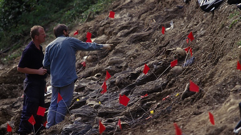 Authorities stand by a mass grave exhumation site near Srebrenica, Bosnia and Herzegovina [File: Laurent Van der Stockt/ Getty Images]