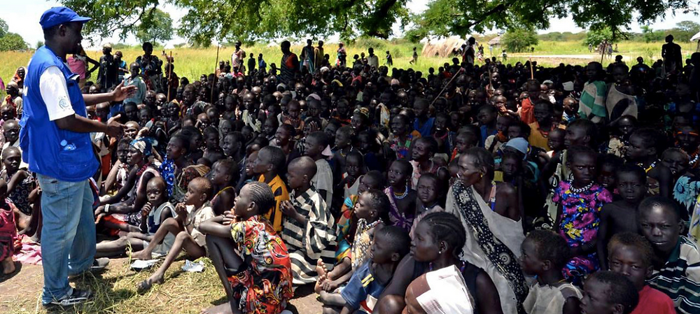 Aid workers register a community affected by hostilities in Jonglei State and explain the process to them which is important to provide food and other assistance. (August 2013)