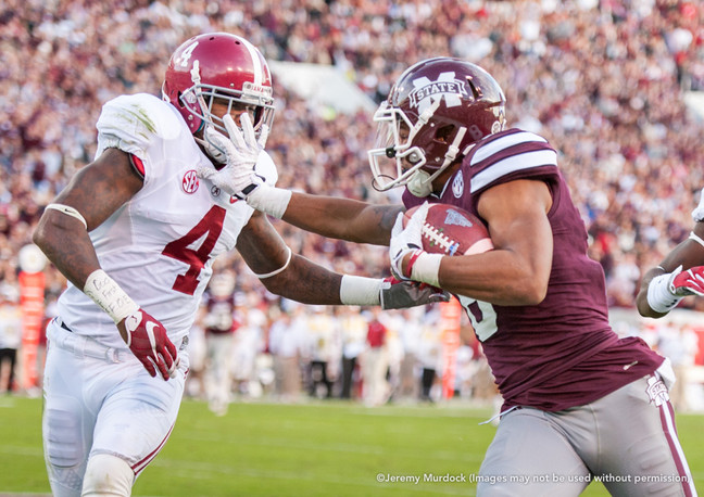 Bulldog receiver delivers a strong stiff arm to an Alabama defender.
