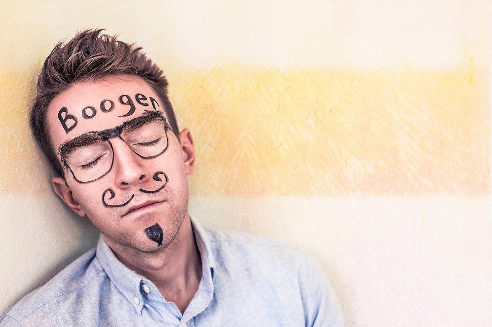 Booger on kirjoitettu nukkuvan miehen otsaan tussilla