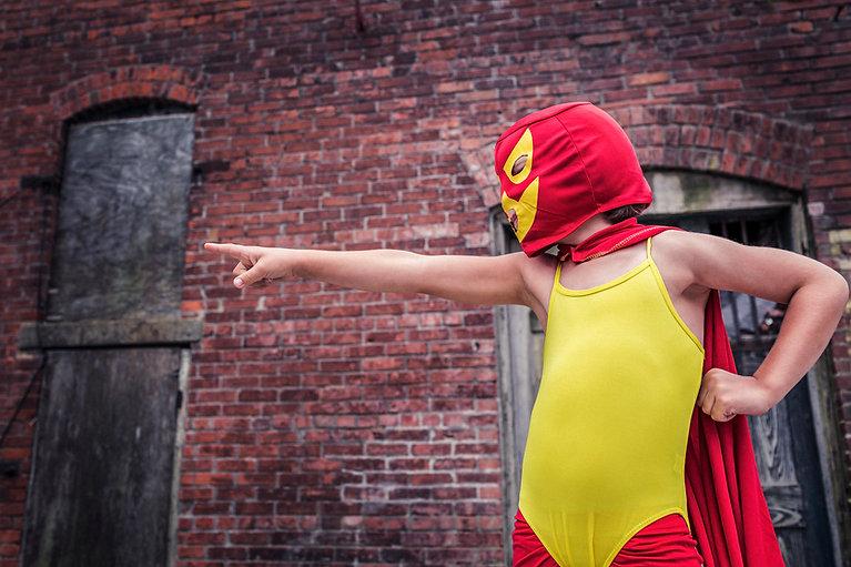 Supersankari naamiopuku lapsi osoittaa punainen tiiliseinä takana