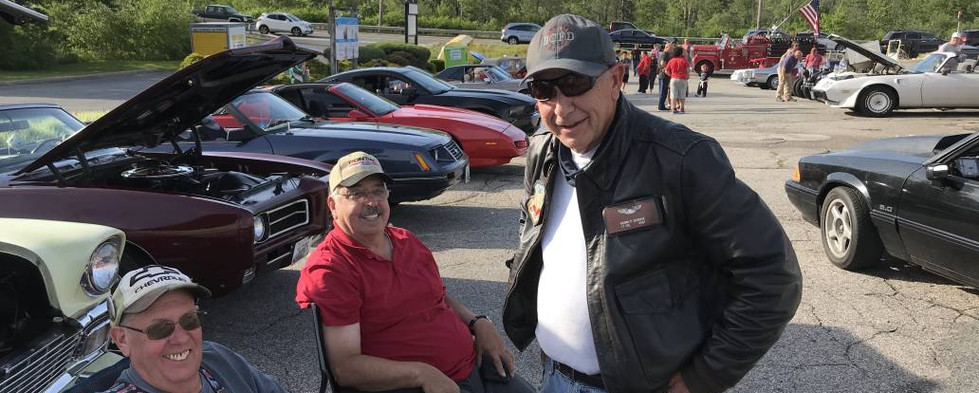 Plenty of smiles from Bob (left), Phil and Dennis (standing).  That's Bob's '56 Chevy and Phil's GTO convertible behind them.