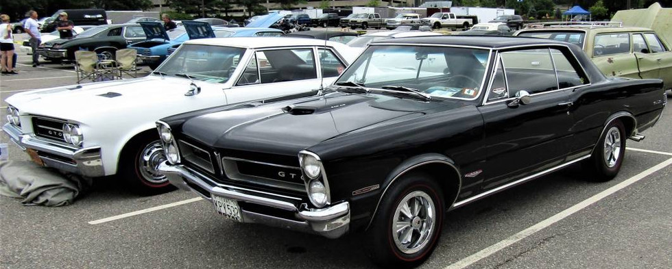Here, a couple early GTOs settled in side-by-side.  That's a white '64 and a black '65.